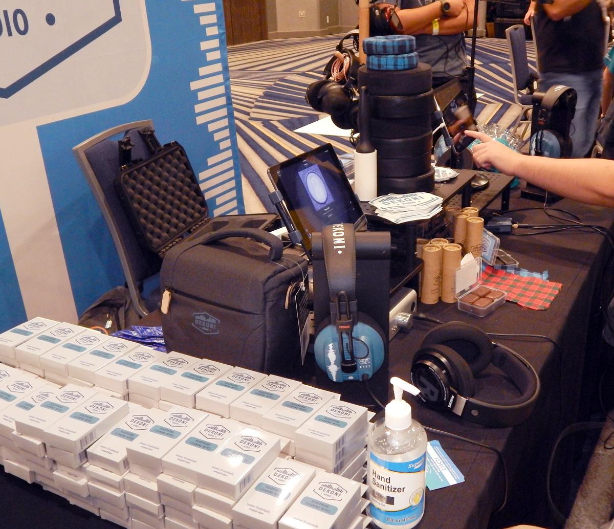 Dekoni headphone wipes, Charcoal Headphone Savior V2 Universal Headphone Carrying Case, Blue Headphones, Headphone Hero (on chair), Headphone Spray, Nuggets Headphone Headband Pressure Relief Pads, and a stack of custom ear-pads CanJam SoCal 2021